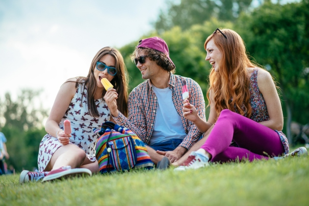 Group of diverse friends eating ice cream in park in early summer