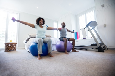 Couple exercising with dumbbells on fitness ball in bedroom