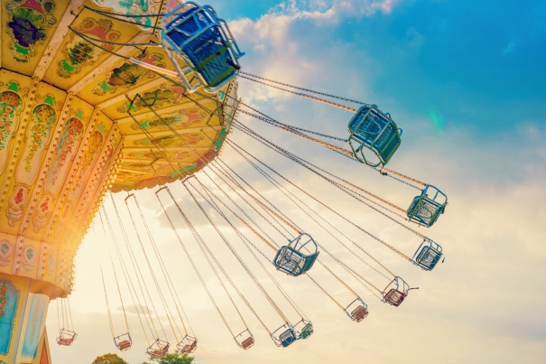 carousel ride spins fast in the air at sunset - a swinging carousel fair ride at dusk