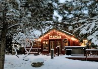 Christmas lights on wooden Colorado mountain country cabin in snow and pine trees