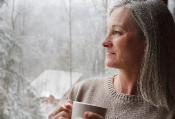 Old woman holds a mug while looking at snow from the window