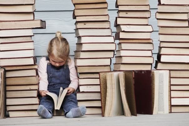 Young girl sits on stack of books